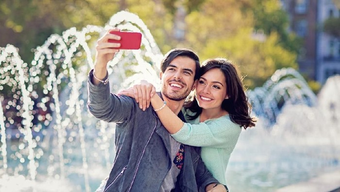 Young couple is hugging and taking selfie at the front of the fountain
