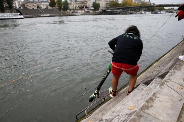 Untuk bisa menarik skuter, dia menggunakan tali yang ujungnya dipasang kait logam. Tak lama kemudian dia menarik tali yang sudah menyangkut di stang skuter dari air (Pascal Rossignol/Reuters)
