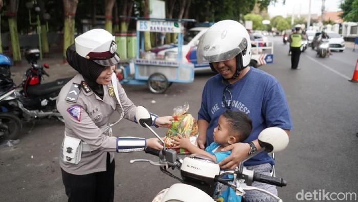 Polwan memberikan hadiah kepada anak pengendara motor. (M Rofiq/detikcom)