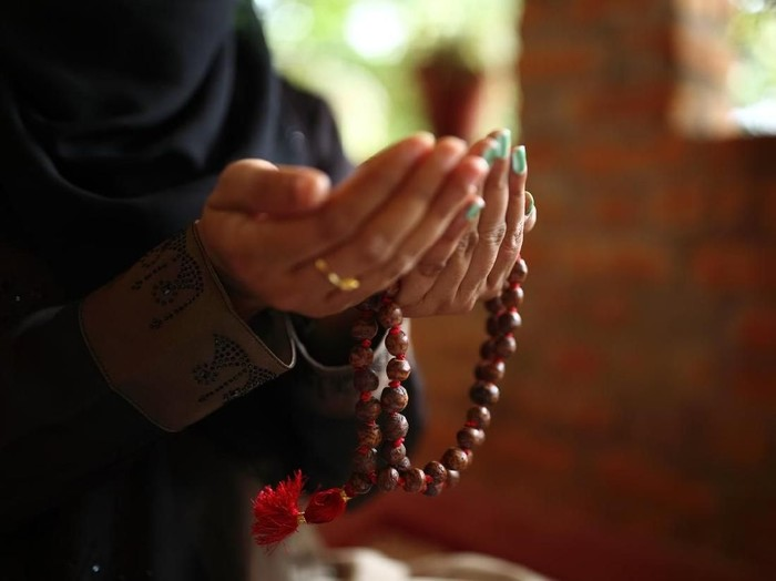 Close-up shot of a Muslim womans hands holding rosary.