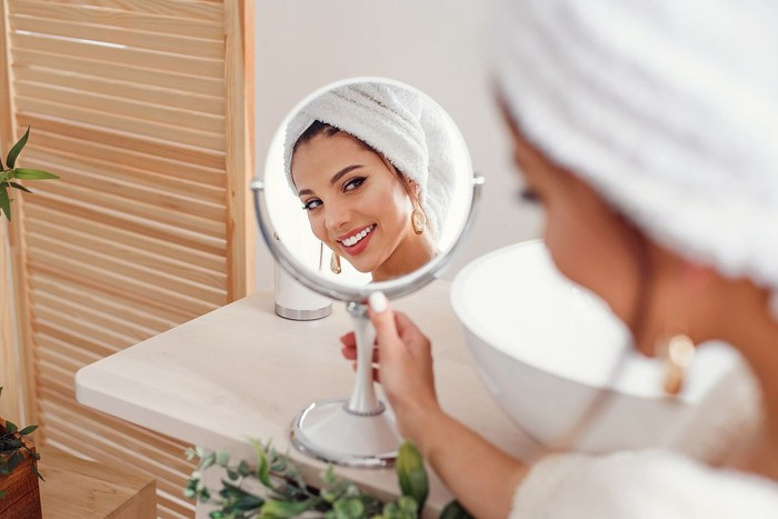 Attractive smiling woman with a white towel on her head dressed in bathrobe looks at herself in the mirror in stylish bathroom after morning shower. Beauty concept.