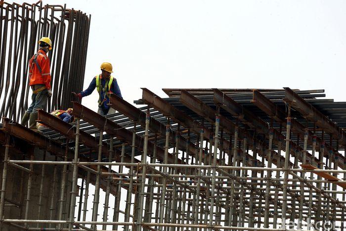 Para pekerja membangun lintasan tol yang membentang dari Bekasi-Cawang-Kampung Melayu.