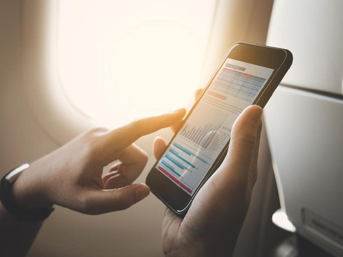 Businesswoman on plane using smartphone with graph on screen.Business technology and travel concepts ideas