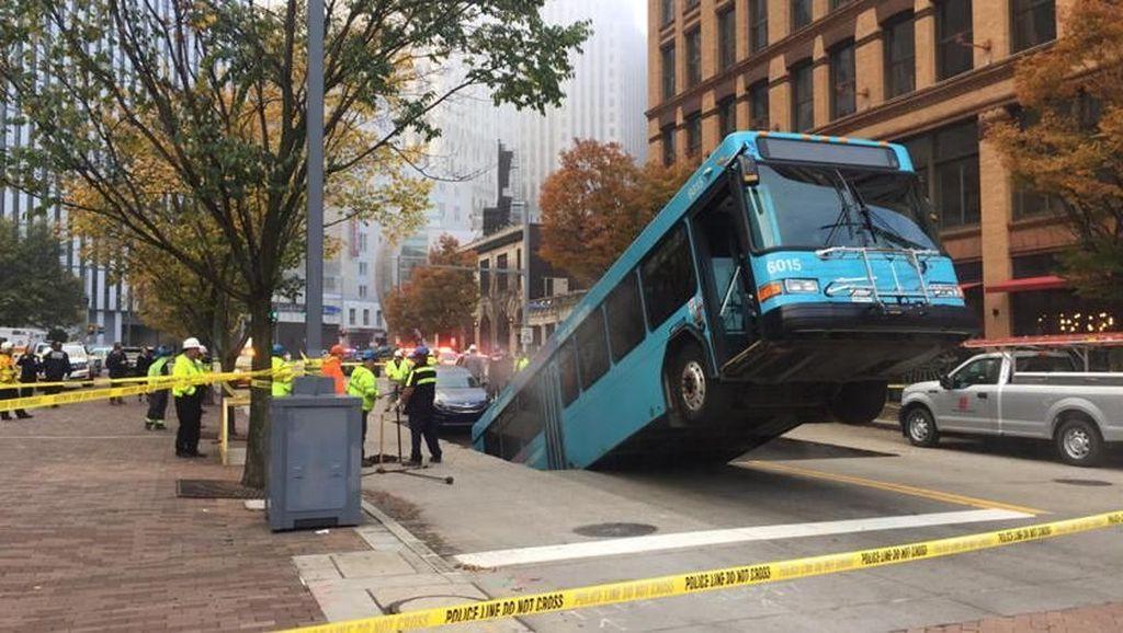 Jalan Amblas Telan Bus dan Hampir Membuat Sedan Terperosok