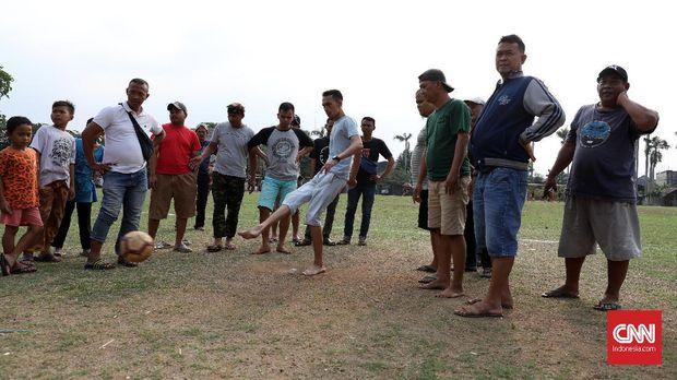 Warga mengadakan taruhan uang sebelum Pertandingan laga Porsegeb Cup IV di Stadion mini Gebyuran, Joglo, Jakarta Barat.