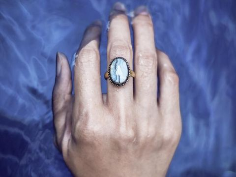 Close up of an antique gold ring with a large shiny blue gemstone on the soft woman hand placed in the water.