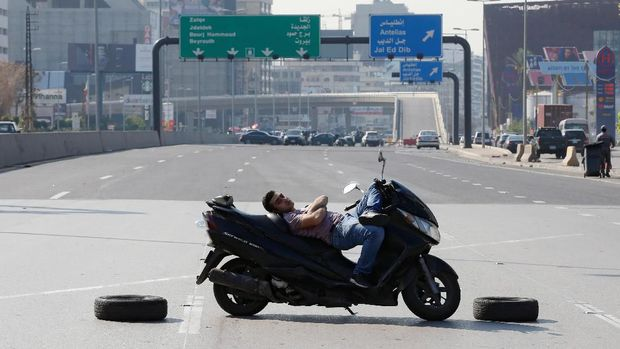 Seorang pria Lebanon tiduran di atas sepeda motornya di ruas jalanan yang diblokir demonstran