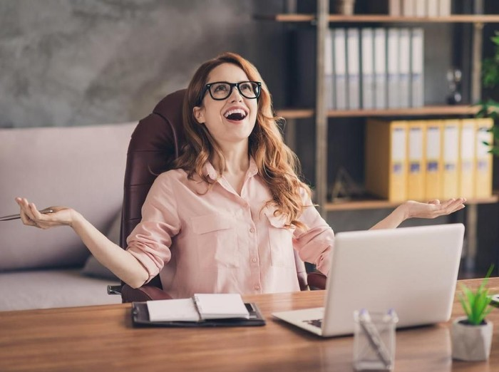 Close up photo beautiful she her business lady hand arm head raised up laugh laughter big salary income earnings genius startup notebook table sit office chair wearing specs formal-wear shirt.