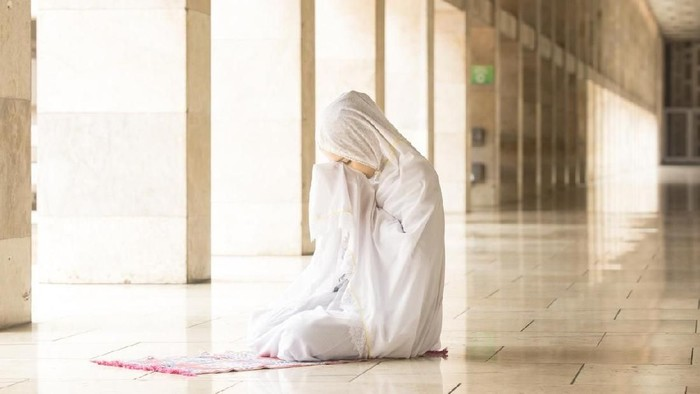 Young muslim woman praying in mosque while wearing prayer veil