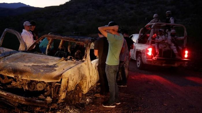 Keluarga korban memeriksa kendaraan korban yang hangus terbakar di Meksiko (REUTERS/Jose Luis Gonzalez)