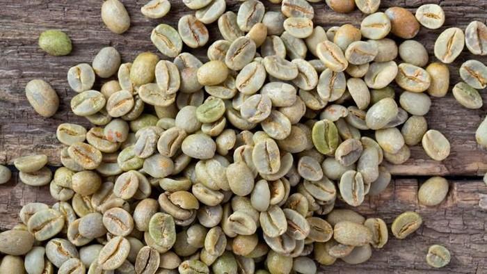 green coffee beans on wooden surfacegreen coffee beans on wooden surface