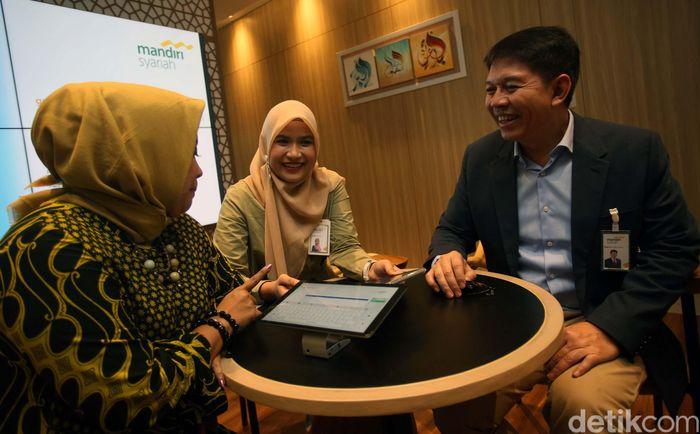 Direktur Utama Mandiri Syariah Toni EB Subari (kanan) mendampingi nasabah melakukan transaksi secara daring di Digital Branch Mandiri Syariah Kantor Cabang Thamrin, Jakarta, Jumat (8/11/2019).