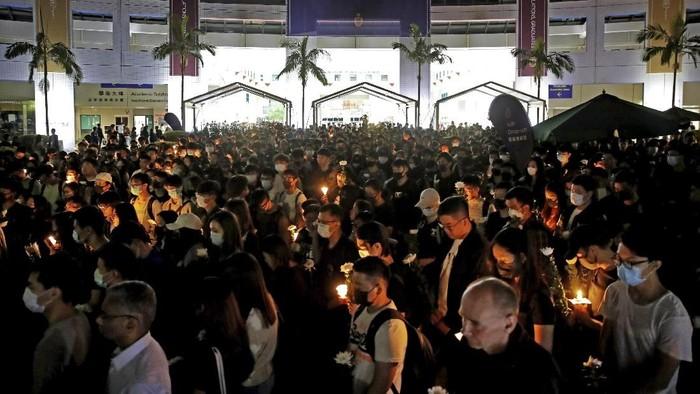 Warga Hong Kong menyalakan lilin saat mendoakan mahasiswa yang tewas dalam bentrokan dengan polisi (AP Photo/Kin Cheung)