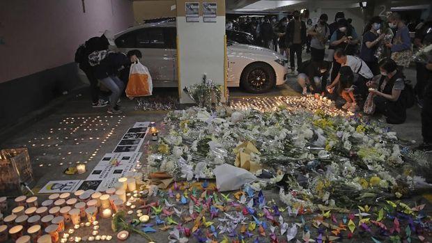 Warga menyalakan lilin, meletakkan karangan bunga dan pesan di lokasi Alex Chow terjatuh saat bentrokan sebelum akhirnya tewas