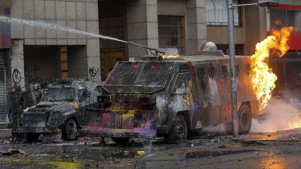 Polisi antihuru-hara bentrok dengan demonstran yang melakukan pembakaran di Santiago