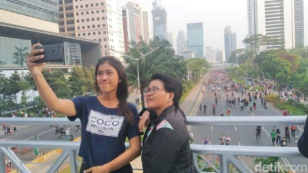 Puput (26) sedang berswafoto di JPO tanpa arap Sudirman