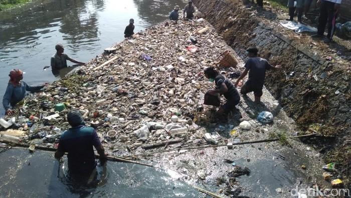 Warga membersihkan Sungai Ledeng yang penuh sampah dan limbah (Foto: Enggran Eko Budianto)