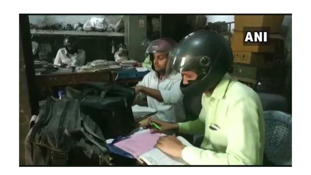 Unik, Karyawan Ini Pakai Helm Motor Selama Bekerja