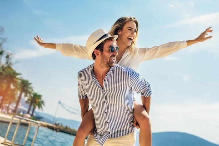 Couple in love, enjoying the summer time by the sea.Joyful girl piggybacking on young boyfriend having fun.
