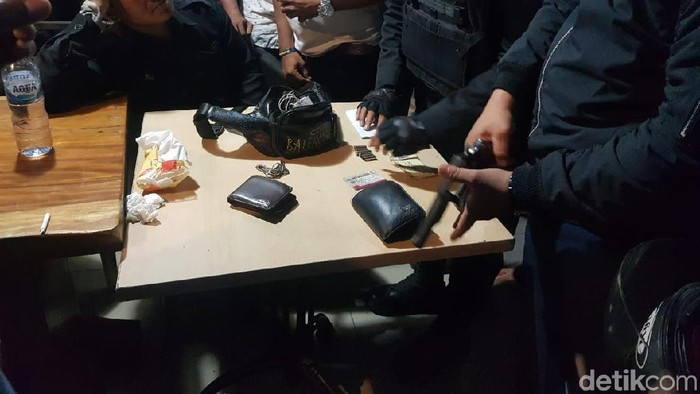 Polisi mengamankan pistol dari pengemudi mobil yang diamuk massa di Pasar Minggu. (Indra Komara/detikcom)