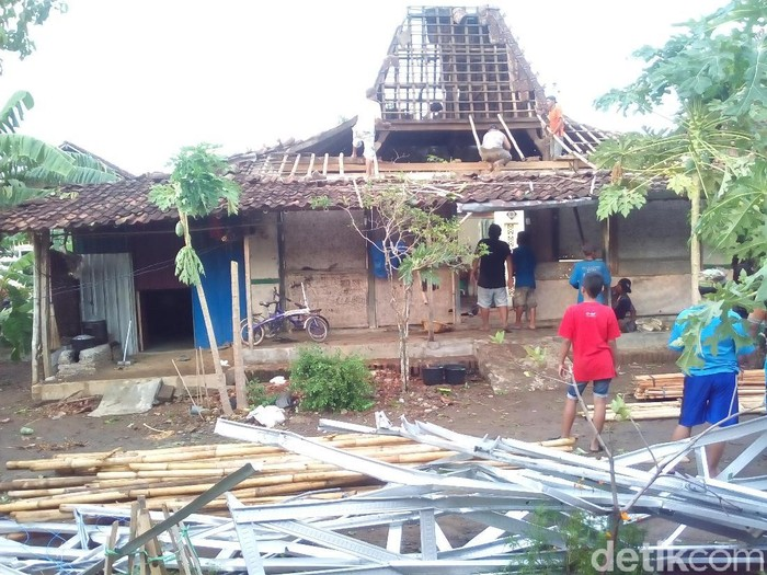 Warga memperbaiki rumah yang rusak terkena angin kencang di Desa Temulus, Mejobo, Kudus, Selasa (12/11/2019). (Akrom Hazami/detikcom)