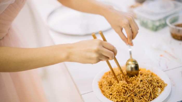 Woman preparing instant noodle on plate in kitchen