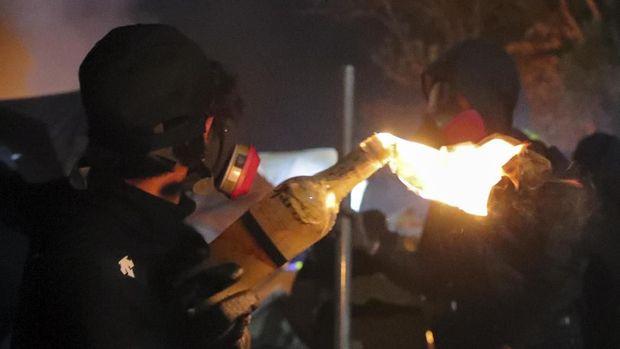 Seorang demonstran Hong Kong memegang bom molotov saat bentrokan dekat kampus setempat