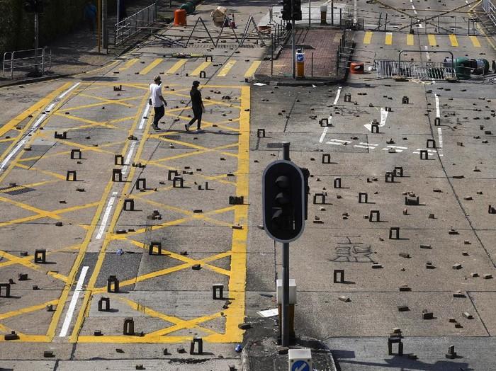 Demonstran Hong Kong meninggalkan dan mengatur bebatuan di tengah jalan untuk memblokir jalanan (AP Photo)