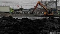 Eksavator tengah melakukan pengerukan lumpur di Kali Ancol, Kamis (14/11/2019).