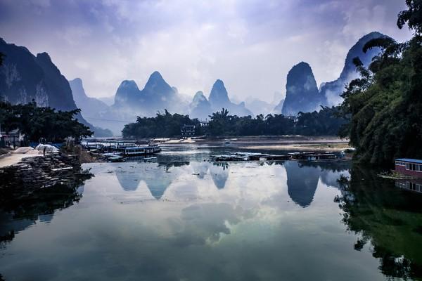Mari mulai membahas keindahan yang dimiliki oleh Li Jiang. Bayangkan sebuah pemandangan sungai yang di kelilingi oleh bukit karst, sedikit tertutup kabut, pepohonan di sisinya dan siluet pagoda dari kejauhan. (iStock)