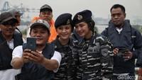 Seorang warga berfoto bersama dua prajurit TNI AL sebelum menaiki Kapal Angkatan Laut (KAL) Kobra di kawasan Pondok Dayung, Jakarta Utara.