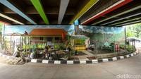 Sejumlah petugas PPSU nampak sedang menyelesaikan pembangunan Taman Betawi yang berada di kolong Tol Jakarta Outer Ring Road West 2 (JORR W 2) Joglo, Jakarta Barat, Kamis (14/11/2019).