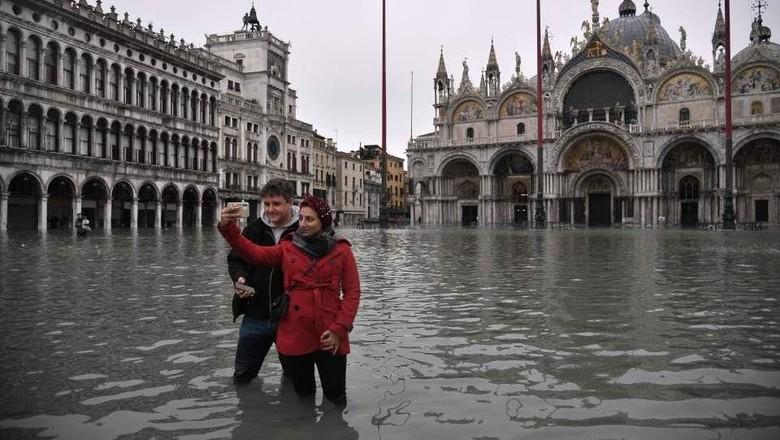 Wisatawan yang foto selfie di tengah banjir Venesia (AFP)