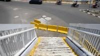 Selain diberikan pembatas jalan, zebra cross nampak tersedia untuk warga yang hendak menuju ke tangga JPO tersebut.