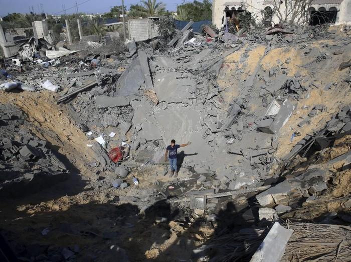 Seorang pemuda Palestina berdiri di tengah kawah yang terbentuk akibat gempuran udara Israel di Gaza (AP Photo/Adel Hana)