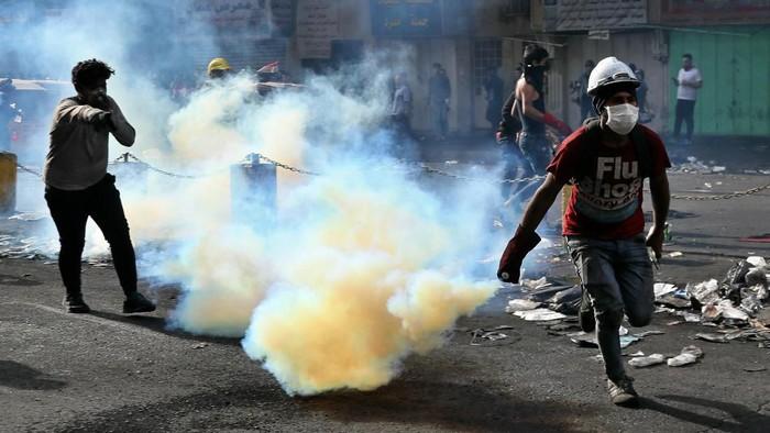 Demonstran antipemerintah di Irak tampak berupaya melemparkan kembali tabung gas air mata yang ditembakkan polisi (AP Photo/Khalid Mohammed)