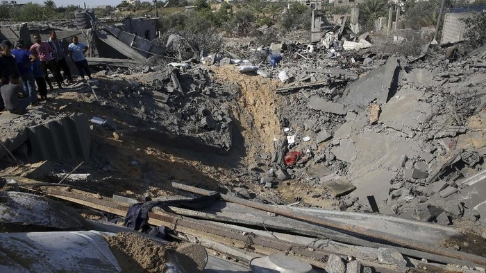 A Palestinian girl looks at the rubble of a destroyed house following overnight Israeli missile strikes, in the town of Khan Younis, southern Gaza Strip, Thursday, Nov. 14, 2019. (AP Photo/Khalil Hamra)