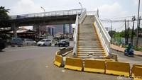 Untuk mengantisipasi terjadinya kecelakaan, pembatas jalan nampak dipasang di area sekitar tangga JPO tesebut.
