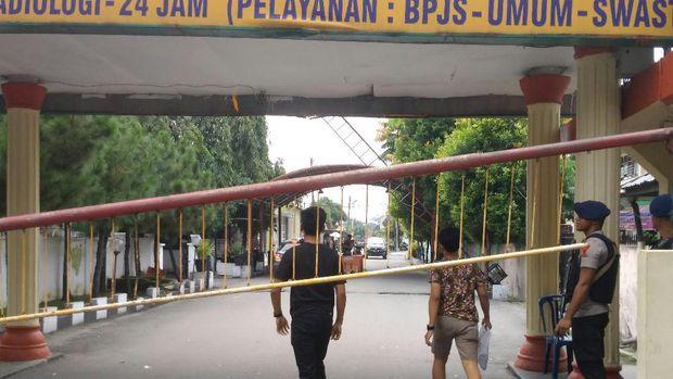 Petugas bersenjata lengkap bersiaga di depan gerbang masuk rumah sakit.