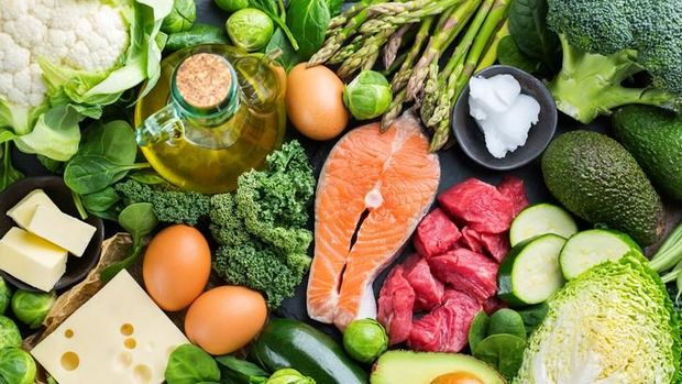Balanced diet nutrition keto concept. Assortment of healthy ketogenic low carb food ingredients for cooking on a kitchen table. Green vegetables, meat, salmon, cheese, eggs. Top view background