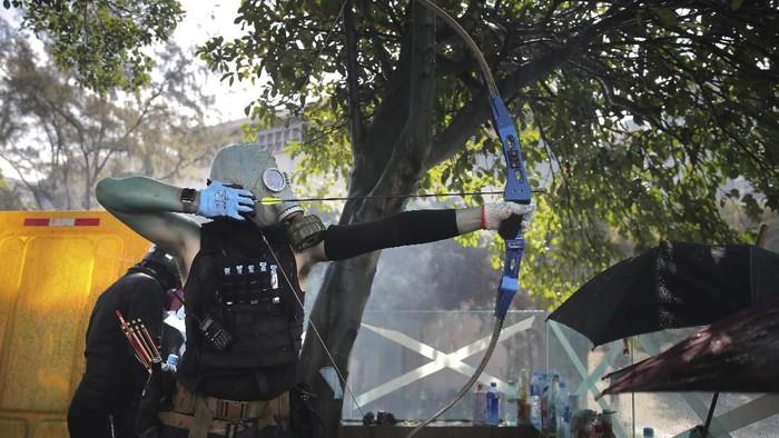 Demonstran Hong Kong menggunakan busur panah dalam bentrokan dengan polisi pada Minggu (17/11) (AP Photo/Kin Cheung)