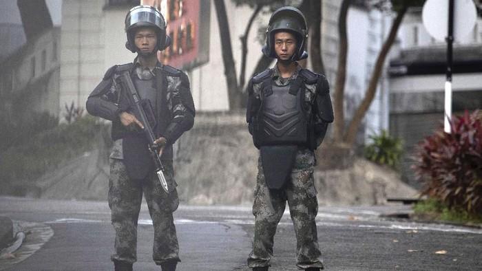 Tentara China berjaga di dalam garnisun mereka di Hong Kong, yang letaknya dekat dengan kampus Universitas Politeknik Hong Kong yang menjadi pusat bentrokan (AP Photo/Ng Han Guan)