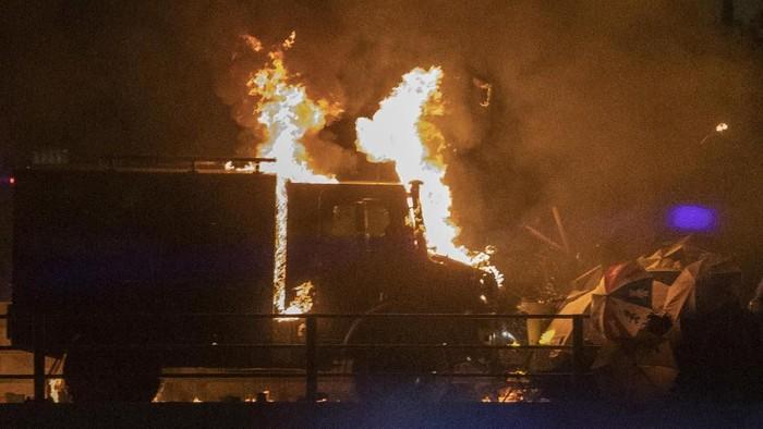 Sebuah kendaraan lapis baja milik polisi Hong Kong terbakar setelah dilempari bom molotov oleh demonstran (AP Photo/Ng Han Guan)