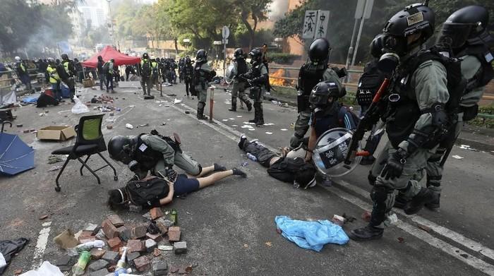 Momen saat polisi Hong Kong menangkap demonstran di sekitar kampus Universitas Politeknik Hong Kong (AP Photo/Achmad Ibrahim)