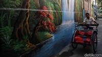 Namun, tak cuma mural bernuansa laut maupun pantai, ada pula mural air terjun yang berada diantara pepohonan rindang nampak tergambar di salah satu dinding di kawasan Kalibaru, Cilincing.