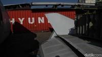 puing-puing pesawat tersebut dikelilingi sejumlah kontainer.