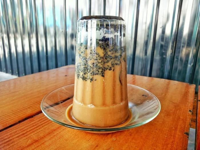 Jalan-jalan ke Aceh wajib coba kopi khop. Kopi disajikan dalam gelas terbalik beralas piring kecil. Cara meminumnya adalah dengan menyesap kopi keluar sedikit demi sedikit dari gelas ke permukaan piring. Slurpp! Foto: Instagram jerang_belanga07
