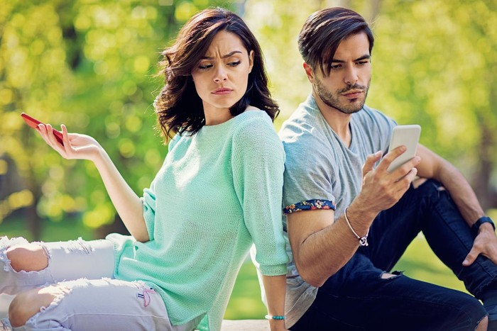 Couple in conflict is texting in the park and sulking each other