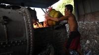Seorang pekerja di pabrik tahu yang berada di Desa Tropodo, Sidoarjo, sedang menambahkan sampah plastik ke tungku pembakaran untuk digunakan sebagai bahan bakar pembuatan tahu.