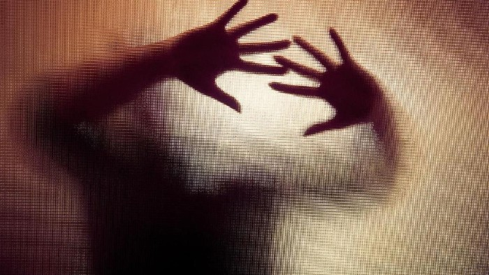 Colour backlit image of the silhouette of a woman with her hands pressed against a glass window. The silhouette is distorted, and the arms elongated, giving an alien-like quality. The image is sinister and foreboding, with an element of horror. It is as if the woman is trying to escape from behind the glass. Horizontal image with copy space.